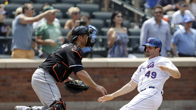 New York Mets' Jonathon Niese (49) slides in to score ahead of the throw to Miami Marlins catcher Jeff Mathis on David Wright's two-run double in the third inning of a baseball game in New York, Sunday, June 9, 2013. (AP Photo/Kathy Willens)