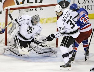 Kings goalie Jonathan Quick blocks a shot by Rangers winger Mats Zuccarello as Willie Mitchell helps defend during Game 3 of the Stanley Cup final Mon...