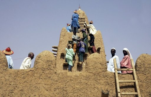 <p>Photo taken in 2006 shows local residents restoring the Djingareyber mosque in Timbuktu. The Islamists controlling northern Mali have destroyed two tombs at the ancient Djingareyber mud mosque in Timbuktu, an endangered World Heritage site, witnesses told AFP.</p>
