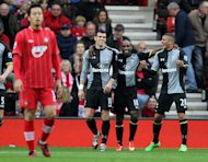 Gareth Bale, left, is congratulated on scoring the opening goal by Jermain Defoe, centre, and Kyle Walker