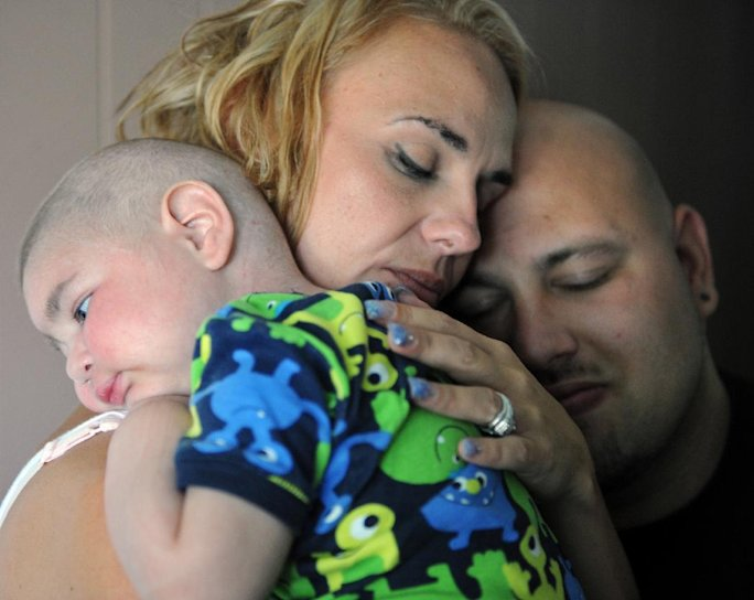 FILE - This July 30, 2013 photo, Christine Swidorsky holds her son, Logan Stevenson, 2, with her husband-to-be and Logan's father Sean Stevenson, for a portrait in their Jeannette, Pa., home. Christine Swidorsky Stevenson says on her Facebook page that Logan died in her arms at 8:18 p.m. Monday, Aug. 5, 2013, at their home. The couple live in Jeannette, about 25 miles east of Pittsburgh, and were wed at a ceremony at their home on Saturday. Logan, who had leukemia and other complications, served as his parents' best man. (AP Photo/Tribune-Review, Eric Schmadel)