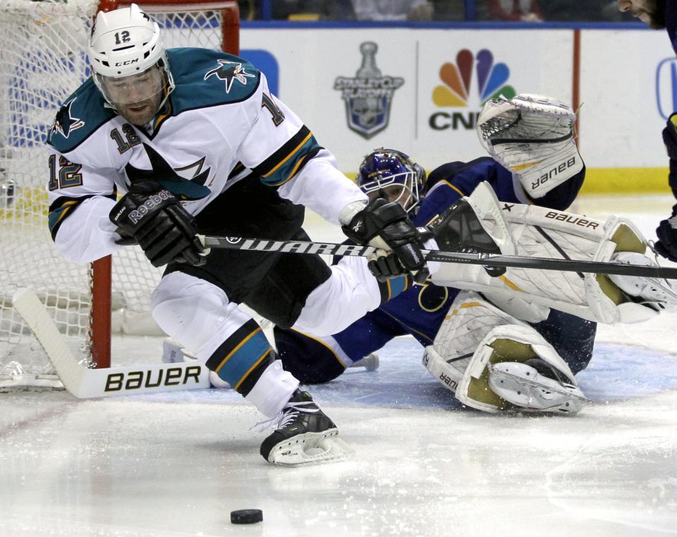 San Jose Sharks' Patrick Marleau, left, falls while chasing a loose puck as St. Louis Blues goalie Brian Elliott, right, defends during the first period in Game 5 of an NHL first-round playoff series hockey game on Saturday, April 21, 2012, in St. Louis. (AP Photo/Jeff Roberson)