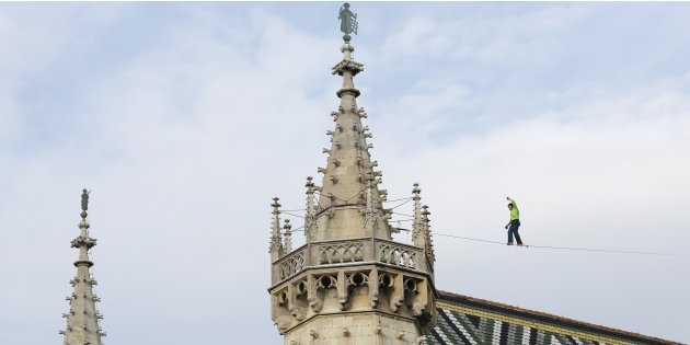 Austrian tightrope walker Christian Waldner passes the roof of St. Stephen's cathedral on a high line in Vienna