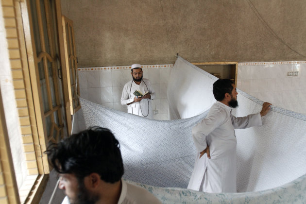 An Afghan Muslim devotee, who lives and prays in isolation in a mosque during Itikaf, the last ten days of the Islamic fasting month of Ramadan, reads from the Quran in the city of Jalalabad east of Kabul, Afghanistan, Tuesday, Aug. 14, 2012. The last ten days of Ramadan, known as Itikaf, are very important according to many Muslims due to the belief that Prophet Muhammad used to exert himself even more in worship, hoping to draw himself closer to God. Itikaf involves total dedication to worship, reading Quran, and supplication. (AP Photo/Rahmat Gul)