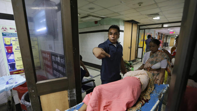 In this Tuesday, Aug. 21, 2012 photo, security guard Amarjeet Singh helps a patient on a stretcher at the Deen Dayal Upadhyay Hospital in New Delhi, India.  Singh and 20 other bouncers have been hired to protect doctors as well as keep the emergency and labor rooms from filling up with patients' often agitated relatives and friends. (AP Photo/Saurabh Das)