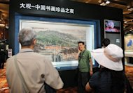 Visitors are seen inspecting a Chinese painting at a preview show of an auction house in Beijing, in May. Until recently, few in the art world had even heard of China's auction houses. Today, they are among the world's biggest by revenue, posing a serious challenge to the likes of Sotheby's and Christie's