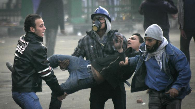 Egyptian protesters carry an injured fellow protester during clashes with military police near Tahrir Square in Cairo, Egypt Saturday, Dec. 17, 2011. Egyptian soldiers clashed with hundreds of rock-throwing protesters in central Cairo for a second consecutive day on Saturday, in a resurgence of turmoil just days after millions voted in parliamentary elections. (AP Photo/Mohammed Abu Zaid)
