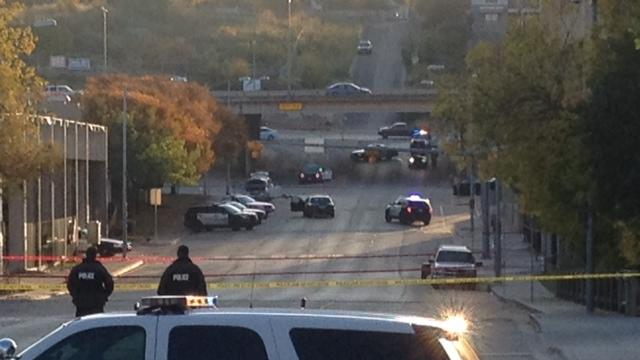 Police tape marks off the scene after authorities shot and killed a man who they say opened fire on the Mexican Consulate, police headquarters and other downtown buildings early Friday, Nov. 28, 2014, in Austin, Texas. In the distance, police cars surround the suspect's vehicle parked near the Interstate 35 overpass. (AP Photo/Jim Vertuno)