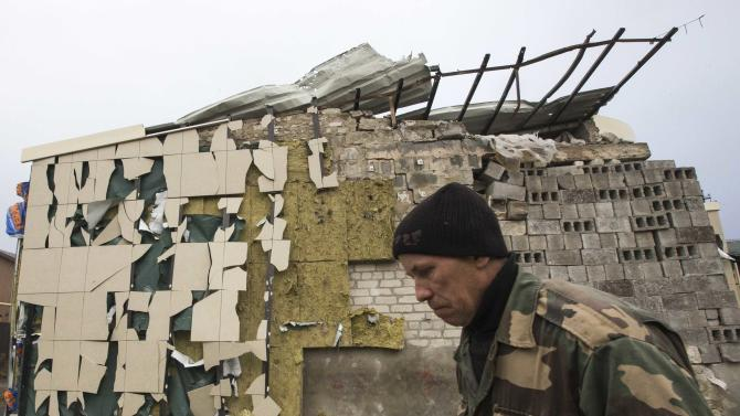 Shramko stands next to a local coffee shop, which was built by his neighbor and damaged by shelling in the village of Spartak, on the outskirts of Donetsk, eastern Ukraine