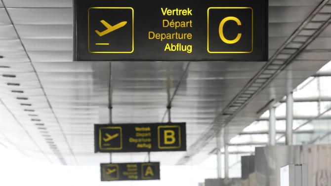 Passengers walk in front of the main entrance of Brussels international airport, Tuesday, Feb. 19, 2013. Eight armed and masked men made a hole in a security fence at Brussels' international airport, drove onto the tarmac and snatched millions of dollars' worth of diamonds from the hold of a Swiss-bound plane without firing a shot, authorities said Tuesday. (AP Photo/Yves Logghe)