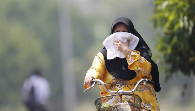 A woman covers her mouth as she cycles in her village amid light haze in Muar