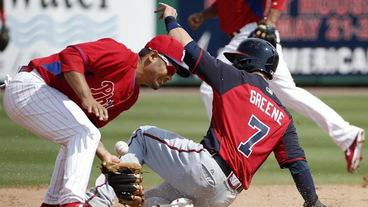 Philadelphia Phillies shortstop Andres Blanco bobbles the throw as Atlanta Braves' Tyler Greene (7) slides safely into second on a seventh-inning stolen base in a spring exhibition baseball game in Clearwater, Fla., Monday, March 10, 2014. The Braves defeated the Phillies 8-1. (AP Photo/Kathy Willens)