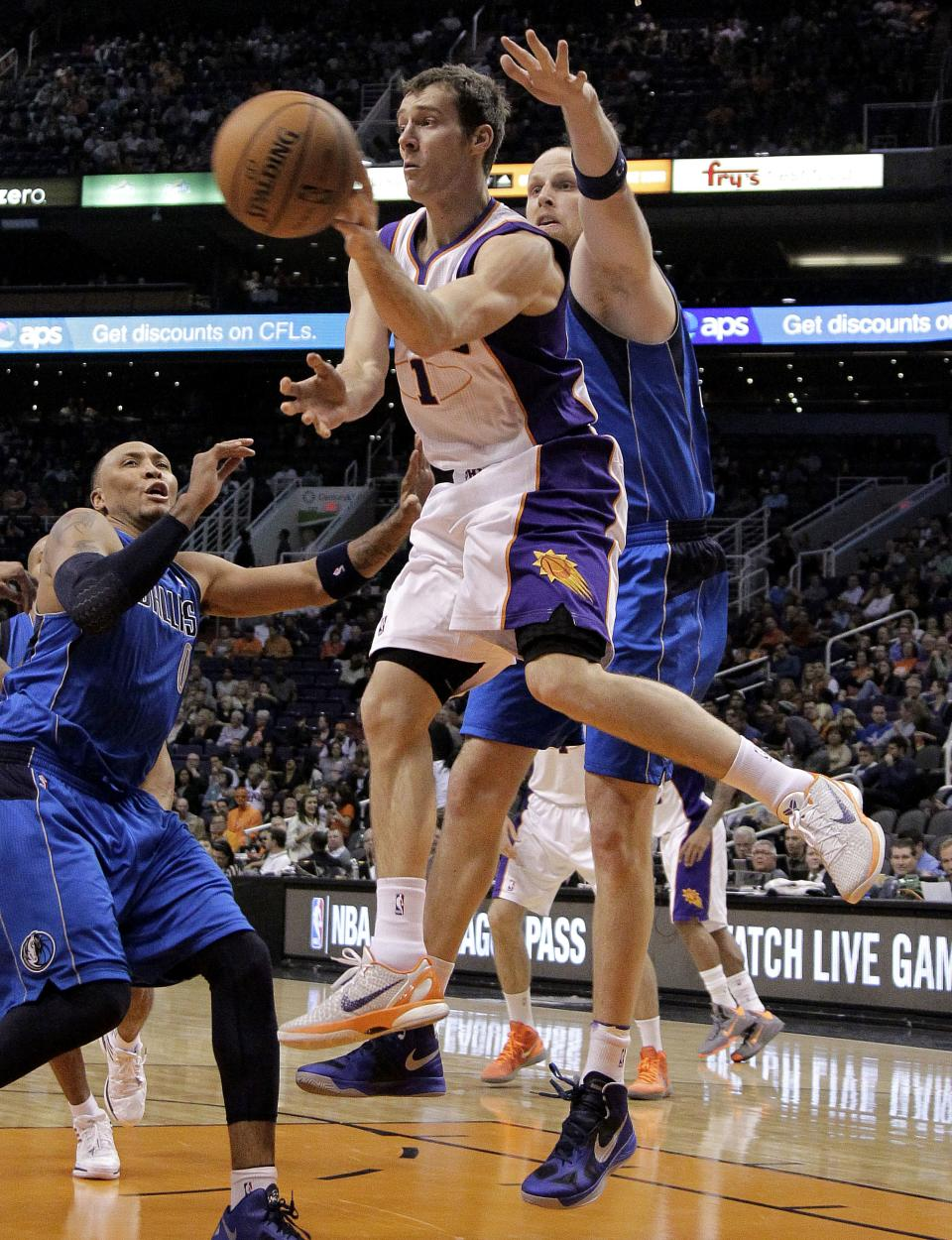 Phoenix Suns' Goran Dragic (1), of Slovenia, passes around the reach of Dallas Mavericks' Chris Kaman during the second half of an NBA basketball game, Thursday, Dec. 6, 2012, in Phoenix. (AP Photo/Matt York)