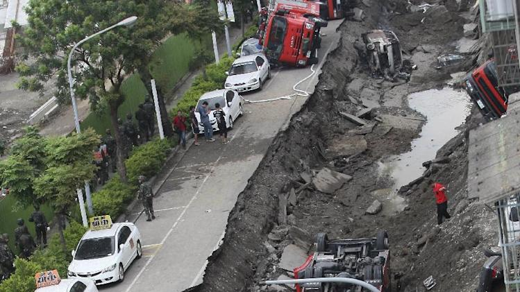 Vehicles are left lie in a destroyed street following multiple explosions from an underground gas leak in Kaohsiung, Taiwan, early Friday, Aug. 1, 2014. A massive gas leakage early Friday caused five explosions that killed scores of people and injured over 200 in the southern Taiwan port city of Kaohsiung. (AP Photo) TAIWAN OUT