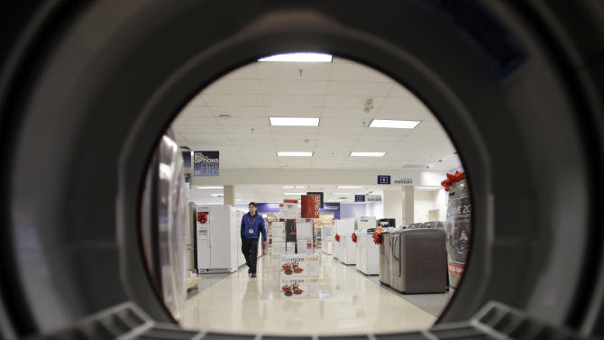 FILE - In this Dec. 6, 2012, photo, an employee walks through the appliance department at a Sears store in North Olmsted, Ohio. Sears' second-quarter loss widened as the number of stores in operation declined and it dealt with lingering effects from its spinoff of the Hometown and Outlet brand, the company reported, on Thursday, Aug. 22, 2013. (AP Photo/Mark Duncan, File)