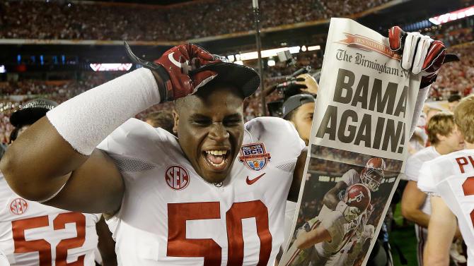 Alabama defensive lineman Alphonse Taylor (50) holds up a newspaper after the BCS National Championship college football game Monday, Jan. 7, 2013, in Miami. Alabama won 42-14. (AP Photo/David J. Phillip)