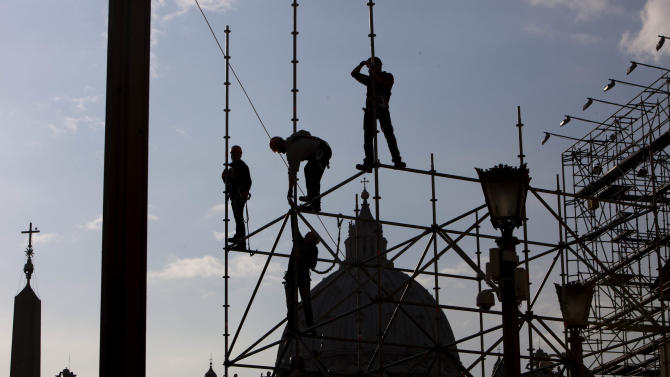 """Workers climb down scaffolding set up for video screens in front of St. Peter's Basilica, ahead of Pope Benedict XVI's last general audience, scheduled for Wednesday, at the Vatican, Tuesday, Feb. 26, 2013. Pope Benedict XVI will be known as """"emeritus pope"""" in his retirement and will continue to wear a white cassock, the Vatican announced Tuesday, again fueling concerns about potential conflicts arising from having both a reigning and a retired pope.The pope's title and what he would wear have been a major source of speculation ever since Benedict stunned the world and announced he would resign on Thursday, the first pontiff to do so in 600 years. (AP Photo/Oded Balilty)"""