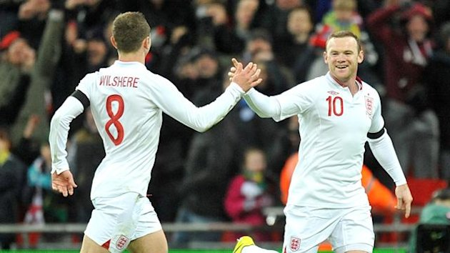 England's Wayne Rooney (right) celebrates with his team-mate Jack Wilshere (left).