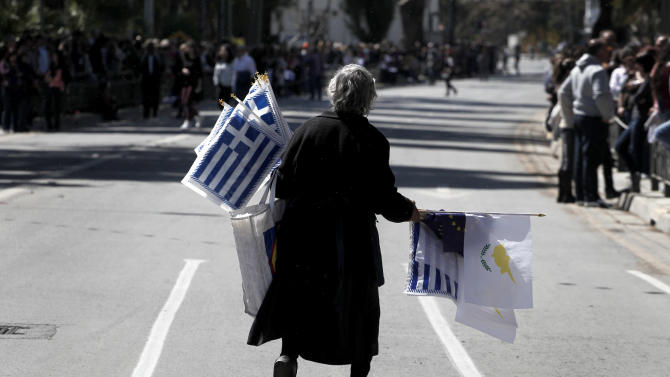 "An elderly woman sells Greek, Cypriot, and EU flags before the start of a parade for Greek Independence Day celebrations in capital Nicosia, Cyprus, Monday, March 25, 2013. Cyprus secured what its politicians described as a ""painful"" solution to avert imminent bankruptcy, agreeing early Monday to slash its oversize banking sector and make large account holders take losses to help pay to secure a last-minute euro10 billion (US$13 billion) bailout. (AP Photo/Petros Giannakouris)"