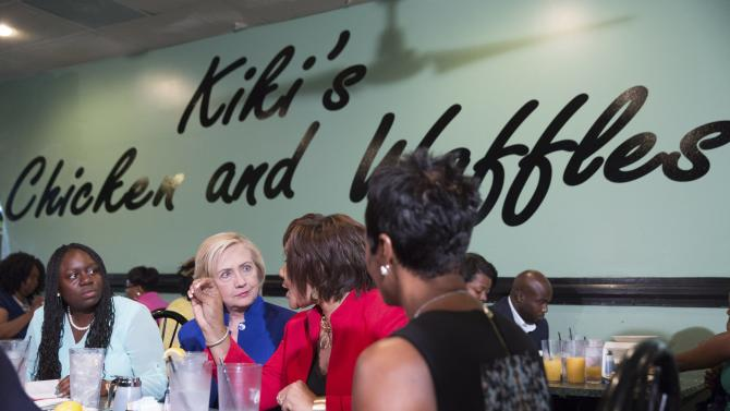 Democratic presidential candidate Hillary Clinton talks with local business leaders while campaigning for the Democratic presidential nomination at Kiki's Chicken and Waffles restaurant in Columbia