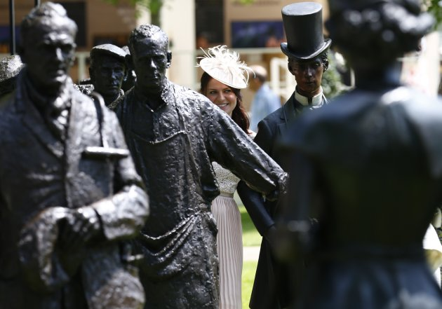 Woman stands amongst statues on second day of the Royal Ascot horse racing festival at Ascot