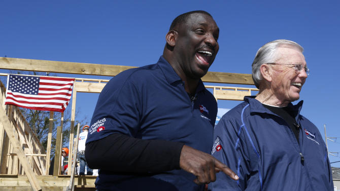 Former NFL head coach Joe Gibbs, right, and Former NFL quarterback and MVP of Super Bowl XXII Doug Williams react during an interview at the launch of M&M'S 'M' Prove America' campaign, which is designed to fund the construction of Habitat for Humanity homes across the country, on Friday, Feb. 1, 2013 in New Orleans. (Jonathan Bachman / AP Images for Habitat For Humanity)