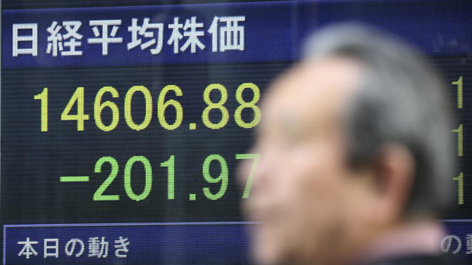 A man walks by an electronic stock price indicator showing the regional heavyweight, Tokyo's Nikkei 225, that shed 201.97 points, or 1.36 percent and closed at 14,606.88, in Tokyo Tuesday, April 8, 2014. Asian stock markets were mixed Tuesday after Japan's central bank refrained from expanding its stimulus and declines in tech stocks weighed on prices. (AP Photo/Eugene Hoshiko)