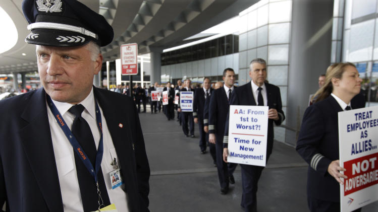 FILE- In this Thursday, Sept. 20, 2012, file photo, Captain Mike McClellan, ORD Domicile Chairman of the Allied Pilots Association left, joins over 200 American Airline pilots marching on a picket line at O'Hare International Airport, in Chicago. There could be progress in breaking the standoff between American Airlines and its pilots that appears to be causing a spike in canceled and delayed flights. American formally asked the pilots' union Tuesday, Sept. 25, 2012, to resume negotiations on a new labor contract. A spokesman said the union board will meet Wednesday to decide on the next step. (AP Photo/M. Spencer Green, File)