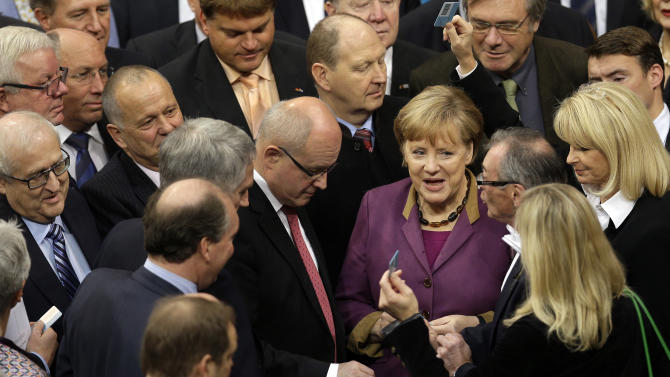 FILE - In this Nov. 30, 3012 file picture German Chancellor Angela Merkel casts her vote at the German federal parliament, Bundestag, in Berlin, Germany, Friday, Nov. 30, 2012. The German Parliament has given its overwhelming backing to a deal aimed at trimming Greece's debt load and keeping the country financially afloat. Lawmakers voted 473-100 on Friday to back the complex deal reached by European finance ministers earlier this week. Germany's chancellor says in an interview published saturday Dec. 1, 2012  she understands the frustration felt by many Germans over the repeated bailout programs for Greece.  But Angela Merkel also insists that helping debt-ridden Greece is in her country's self-interest because it helps stabilize the 17-nation eurozone on which Germany's prosperity depends.  (AP Photo/Michael Sohn,File)