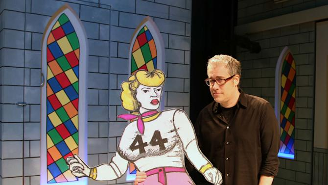 "This Jan. 18, 2013 photo shows Playwright and TV writer Rolin Jones posing with a cardboard prop from his new play, ""The Jammer,"" onstage at the Atlantic Theater Company in New York. Jones, whose play ""The Intelligent Design of Jenny Chow"" was a Pulitzer Prize finalist, turns his attention to roller derby.  (AP Photo/Mark Kennedy)"