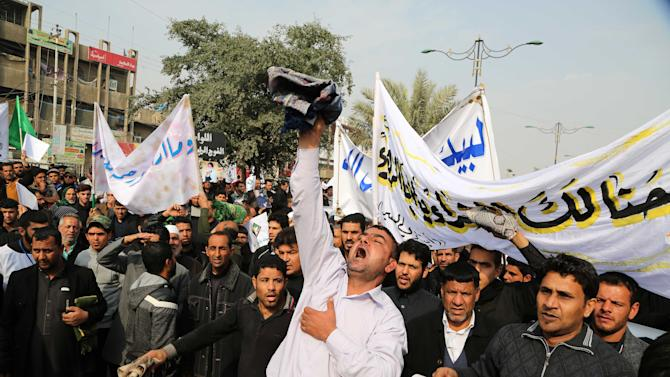 Iraqi demonstrators chant angry slogans during a protest against caricatures of the Prophet Muhammad published in the satirical French weekly magazine Charlie Hebdo, in the Shiite neighborhood of Sadr city in Baghdad, Iraq, Friday, Jan. 30, 2015. (AP Photo/Karim Kadim)