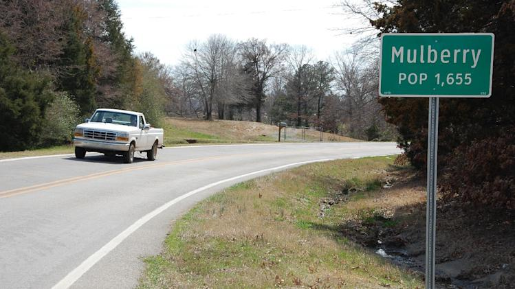 A truck drives near a population sign in Mulberry, Ark., on Wednesday, March 13, 2013. (AP Photo/Jeannie Nuss)