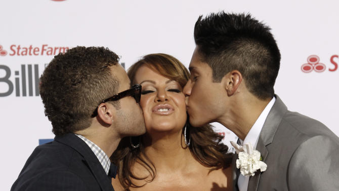 In this April 26, 2012, file photo, Singer Jenni Rivera, center, is kissed by singers Nacho, left, and Chino, right, as they walk the red carpet at the Latin Billboard Awards in Coral Gables, Fla. The wreckage of a small plane believed to be carrying Mexican-American music superstar Jenni Rivera was found in northern Mexico on Sunday, Dec. 9, 2012, and there are no apparent survivors, authorities said.  (AP Photo/Wilfredo Lee, file)