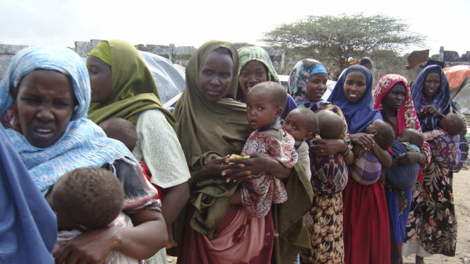 Somali women   from southern Somalia holding babies stand in a line to receive aid at a refugee camp  in Mogadishu, Somalia, Saturday, July 16, 2011. Thousands of people have arrived in Mogadishu over the past two weeks seeking assistance and the number is increasing by the day, due to lack of water and food. The worst drought in the Horn of Africa has sparked a severe food crisis and high malnutrition rates, with parts of Kenya and Somalia experiencing pre-famine conditions, the United Nations has said. More than 10 million people are now affected in drought-stricken areas of Djibouti, Ethiopia, Kenya, Somalia and Uganda and the situation is deteriorating. (AP Photo/Farah Abdi Warsameh)