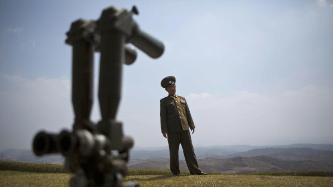 North Korean Army Col. Kim Chang Jun, stands behind field binoculars on a hilltop overlooking the demilitarized zone which separates the two Koreas in south of Kaesong, North Korea, Wednesday, April 24, 2013. For weeks, North Korea has threatened to attack the U.S. and South Korea for holding joint military drills and for supporting U.N. sanctions. Washington and Seoul said they've seen no evidence that Pyongyang is actually preparing for a major conflict, though South Korean defense officials said the North appears prepared to test-fire a medium-range missile. (AP Photo/David Guttenfelder)