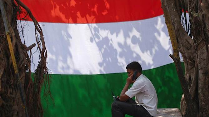A man speaks on the phone outside his shanty in front of an Indian national flag in Dharavi, one of Asia's largest slums, in Mumbai