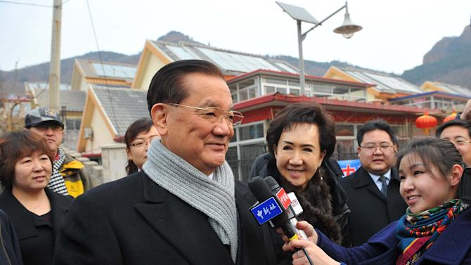 In this photo provided by China's Xinhua News Agency, Taiwan's Kuomintang Honorary Chairman Lien Chan, center, speaks to the media after visiting the village of Guajiayu on the outskirts of Beijing, China, Tuesday, Feb. 18, 2014. Lien, also chairman of a foundation on cross-Strait peaceful development, is leading a delegation from Taiwan for a four-day visit to the Chinese mainland. (AP Photo/Xinhua, Chen Yehua) NO SALES