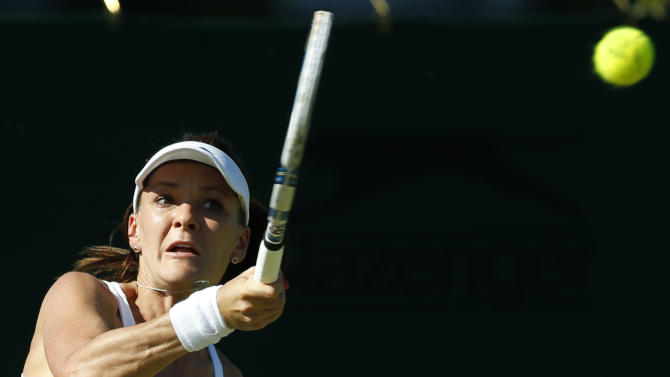 Agnieszka Radwanska of Poland returns a ball to Lucie Hradecka of the Czech Republic during the singles first round match at the All England Lawn Tennis Championships in Wimbledon, London, Tuesday June 30, 2015. (AP Photo/Alastair Grant)