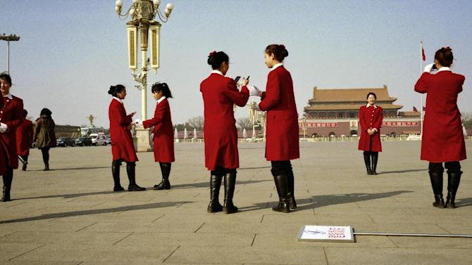 In this Sunday, March 3, 2013 photo, hotel hostesses, who serve delegates of the Chinese People's Political Consultative Conference take souvenir photos at Tiananmen Square,  which is closed to the public to function as a parking lot for buses transporting delegates, while the opening session of the CPPCC is held in the nearby Great Hall of the People in Beijing, China. (AP Photo/Alexander F. Yuan)