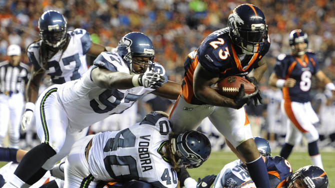 Denver Broncos running back Willis McGahee (23) lunges through the defense of Seattle Seahawks defensive end Jimmy Wilkerson (97) and cornerback David Vobora to cross the goal line for a touchdown in the second quarter of a preseason NFL football game, Saturday, Aug. 27, 2011, in Denver. (AP Photo/Jack Dempsey)
