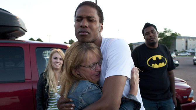 "Judy Goos, center left, hugs her daughter's friend, Isaiah Bow, 20, while eyewitnesses Emma Goos, 19, left, and Terrell Wallin, 20, right, gather outside Gateway High School where witnesses were brought for questioning Friday, July 20, 2012, in Aurora, Colo. A gunman wearing a gas mask set off an unknown gas and fired into a crowded movie theater at a midnight opening of the Batman movie ""The Dark Knight Rises,"" killing at least 12 people and injuring at least 50 others, authorities said. (AP Photo/Barry Gutierrez)"