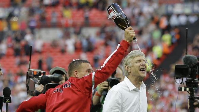 Arsenal's coach Arsene Wenger is doused with champagne by Lukas Podolski as they celebrate after winning the English FA Cup final soccer match between Arsenal and Hull City at Wembley Stadium in London, Saturday, May 17, 2014. Arsenal won 3-2 after extra-time