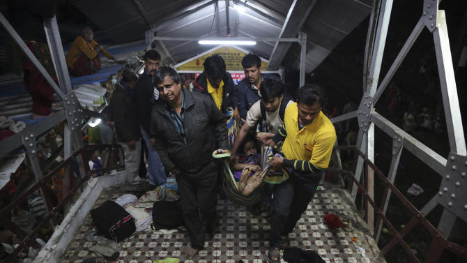 Indian men carry the body of a woman killed in a stampede on the railway platform where the incident occurred at the main railway station in Allahabad, India, Sunday, Feb. 10, 2013. At least ten Hindu pilgrims attending the Kumbh Mela were killed and more then thirty were injured in a stampede on an overcrowded staircase, according to Railway Ministry sources.  (AP Photo/Kevin Frayer)