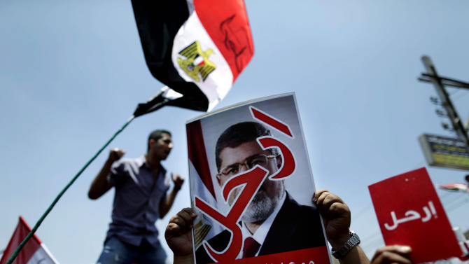"Opponents of Egypt's Islamist President Mohammed Morsi hold posters with Arabic that reads, ""Leave,"" as they protest outside the presidential palace in Cairo, Egypt, Sunday, June 30, 2013. Organizers of a mass protest against Morsi claimed Saturday that more than 22 million people have signed their petition demanding the Islamist leader step down, asserting that the tally was a reflection of how much the public has turned against his rule. (AP Photo/Hassan Ammar)"