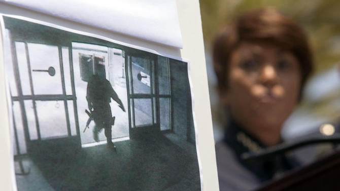 A picture of the suspect entering Santa Monica College Library is seen as Jacqueline Seabrook, Chief of Santa Monica Police department speaks during a news conference Saturday June 8, 2013, in Santa Monica, Calif.,  to discuss more information regarding the suspect in the shooting that left five people dead, including the shooter, near Santa Monica College on Friday. (AP Photo/Ringo H.W. Chiu)