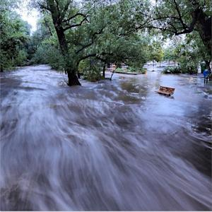 In this image made with a slow shutter speed which blurred the rushing water, flood waters course through a small park in Boulder, Colo., Thursday morning, Sept. 12, 2013. Heavy rains and scarring from recent wildfires sent walls of water crashing down mountainsides in the area. (AP Photo/Jud Valeski)
