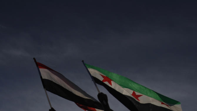 A boy holds Yemen's flag, left, and Syrian flag, right, during a rally to show support for President Abed Rabbu Mansour Hadi, in Sanaa, Yemen, Thursday, Dec. 20, 2012. (AP Photo/Hani Mohammed)