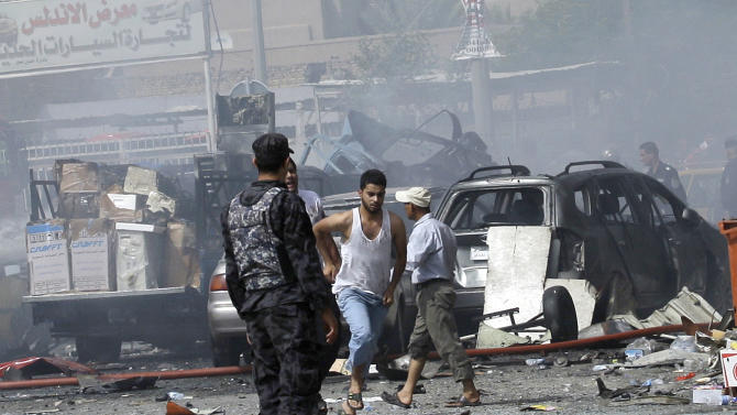 People and security forces gather at the scene of a car bomb explosion in a shopping area in Karradah, Baghdad, Iraq, Tuesday, July 31, 2012. Iraqi officials say twin car bombings within five minutes of each other have killed and wounded scores of people. (AP Photo/Khalid Mohammed)