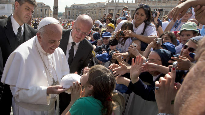 Pope Francis exchanges skull caps with a young girl after stepping out of his pope-mobile to walk the last part of his way to the altar, to deliver his weekly general audience in St. Peter's Square at the Vatican, Wednesday, May, 8, 2013.  (AP Photo/Alessandra Tarantino)