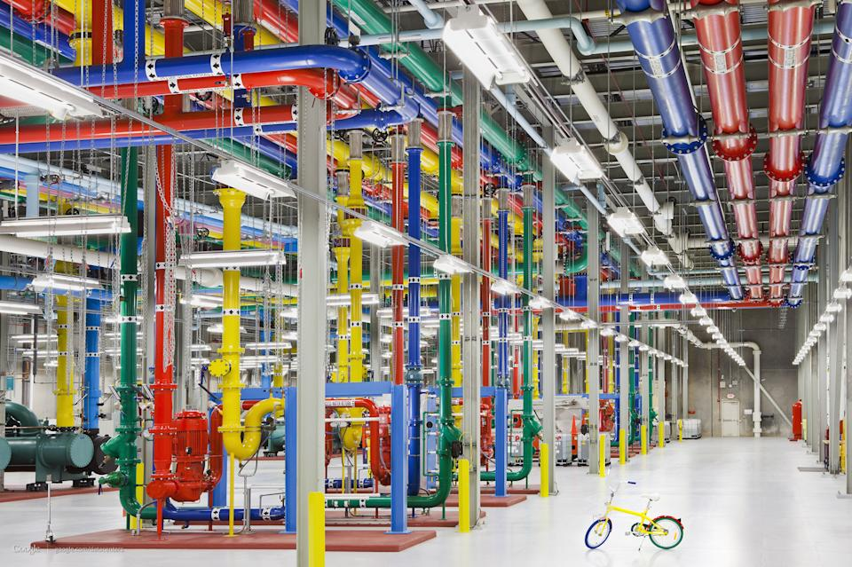 This undated photo made available by Google shows colorful pipes sending and receiving water for cooling Google's data center in Douglass County, Ga. On the right is a G-Bike, which the company says is the vehicle of choice for employees to travel around the vast centers. (AP Photo/Google, Connie Zhou)